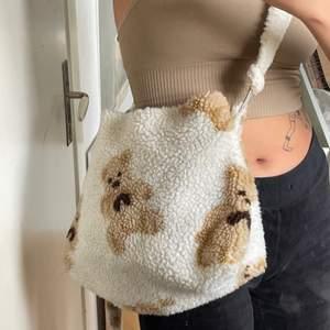 Vit fluffig väska med nallebjörnar på med längre reglerbart band. Frakt tillkommer!!
