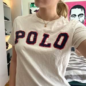 En stilren vit T-shirt med sytt POLO tryck. Köpt i Schweiz. Storlek M. Passar både herr och dam 😊