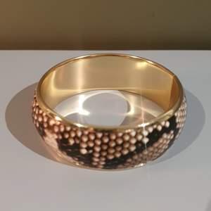 Snyggt armband, guldigt och snakeprint. Snyggt till vitt eller minimalistiskt svart/beige.