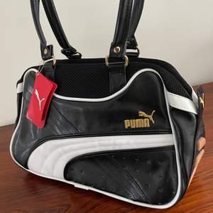 Supersnygg svart Puma väska med vita och guldiga detaljer. Helt oanvänd med prislappen kvar och köpt från USA!🙂 Det finns en innerficka utan dragkedja inuti väskan. Kontakta vid fler bilder, frågor eller vid intresse. Frakt tillkommer!✨