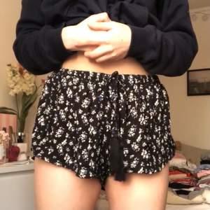 Ett par blommiga shorts som ser ut som en kjol på. Snörning längst fram. Väldigt stretchiga i midjan. Köparen står för frakten men möter även upp i Lund!