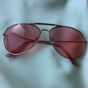 Solglasögon med rosa glas.