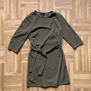 Militärgrön miniklänning med tillhörande skärp från Amisu. Använd endast en gång, och i fint skick! Kommer inte till användning så säljer den här 🥰 Nypris 219.-