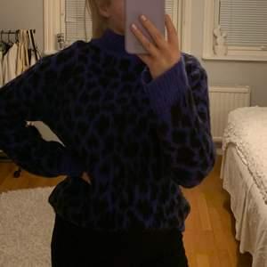 Stickad tröja i blå-svart leopardmönster från Nakd i storlek XS. Stor i storleken. Använd fåtal gånger, normalt slitage.