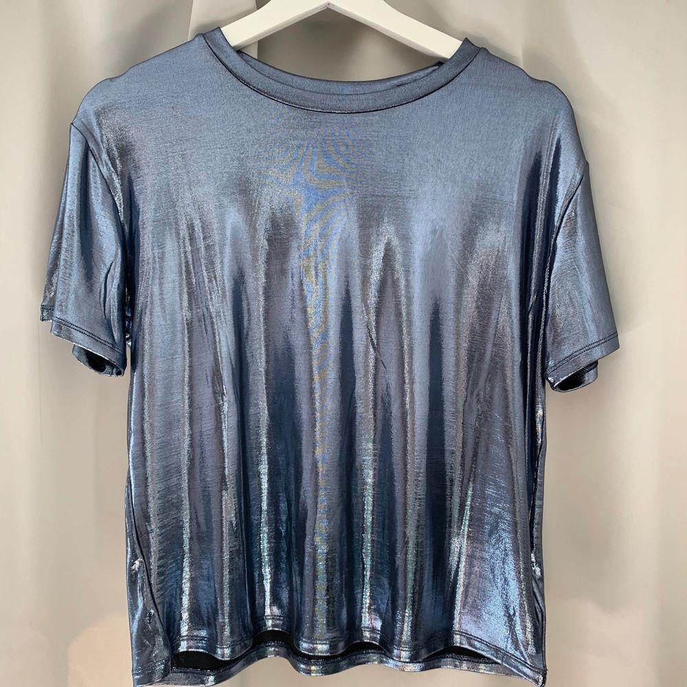 Säljer min silvrig/glansiga t-shirt från hm, aldrig kommit till användning så den är i nyttskick!! köparen står för frakten!😘. T-shirts.