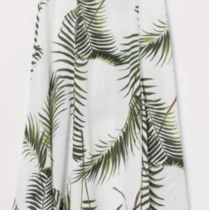 En vadlång, cirkelskuren kjol i crêppad, vävd kvalitet med tryckt mönster. Kjolen har hög midja och dold dragkedja i sidan. Hög slits fram. Ofodrad.
