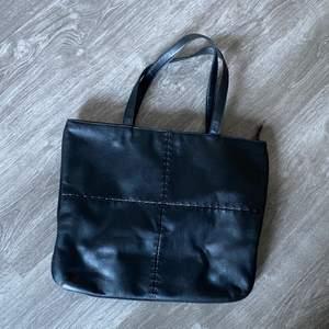 Svart väska med korta axelband. Du får ändå den över axeln om du vill det. Du får plats med laptop i den. Den är använd men i gott skick. (Inte äkta läder) FRAKT ÄR INKLUDERAT I PRISET⚡️⚡️