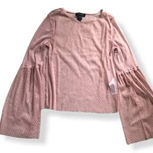 Superfin transparent tröja som är väldigt snygg att ha på sig med en crop top under.den är rosa genomskinlig och prickig. Ärmarna är väldigt vida. Storlek 38.