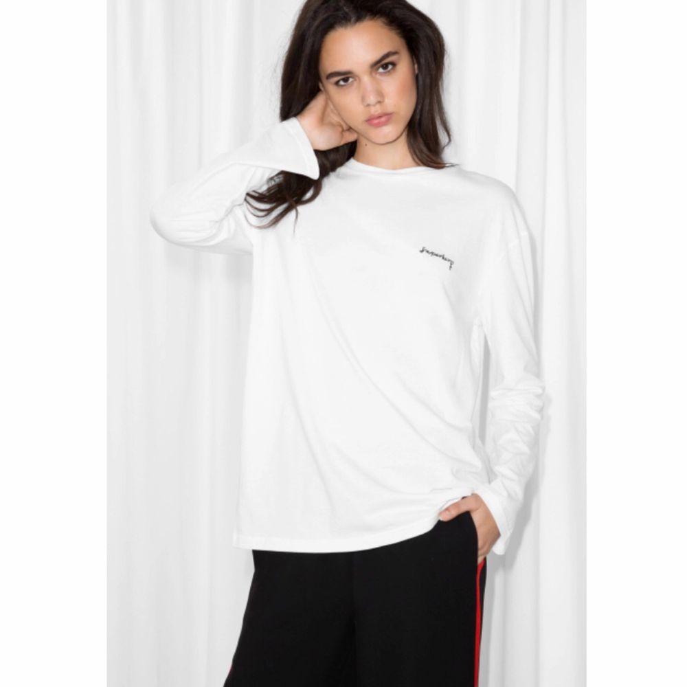 Feministiskt «Superhero» vit långärmad tröja & Other Stories i bomull. Oversize st.34, passar 34 till 38. Fint skick, använd två gånger och inget att anmärka på. Längd:67cm - 100% bomull. Toppar.