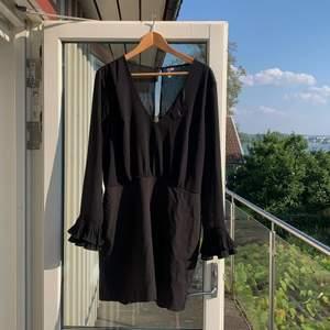 Relativt oanvänd klänning med öppen rygg och volangärmar. Ena knappen i ryggen har gått sönder men kan lätt lagas. Köparen står för frakt.