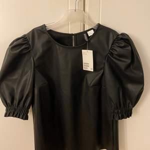 En skinn tröja från hm i storlek 34 OBS: EJ ÄKTA SKINN! Helt oanvänd med lapen kvar. 100 kr!