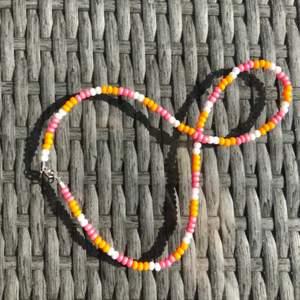 Handgjort halsband i orange, rosa och vita pärlor 🥰 frakten ingår