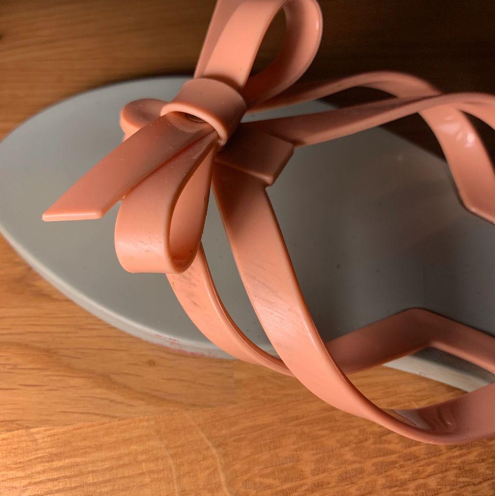 Turkosa sandaler med en rosa rosettdetalj på. Bra hållbarhet. Har några repor här och där men de syns bara på nära håll. Undesidorna är rätt missfärgade men det syns ju inte när man har dem på sig dem. 50kr + frakt🌶. Skor.