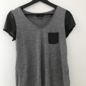 Grå t-shirt med svarta ärmar i tunnt skinnliknande material i storlek 36/38. Har använts en hel del och är lite sliten i ärmarna men annars är tröjan i bra skick.