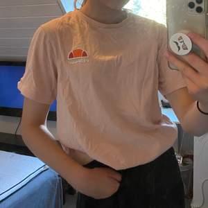 En rosa tröja från ellesse med deras märke på vänster bröst. Snygg passform då den är något oversized.