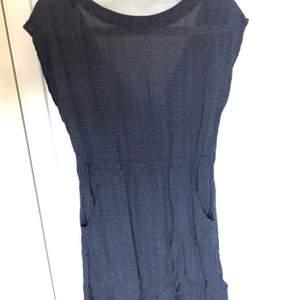 Marinblå klänning med små prickar, första bilden är framifrån, aldrig använd
