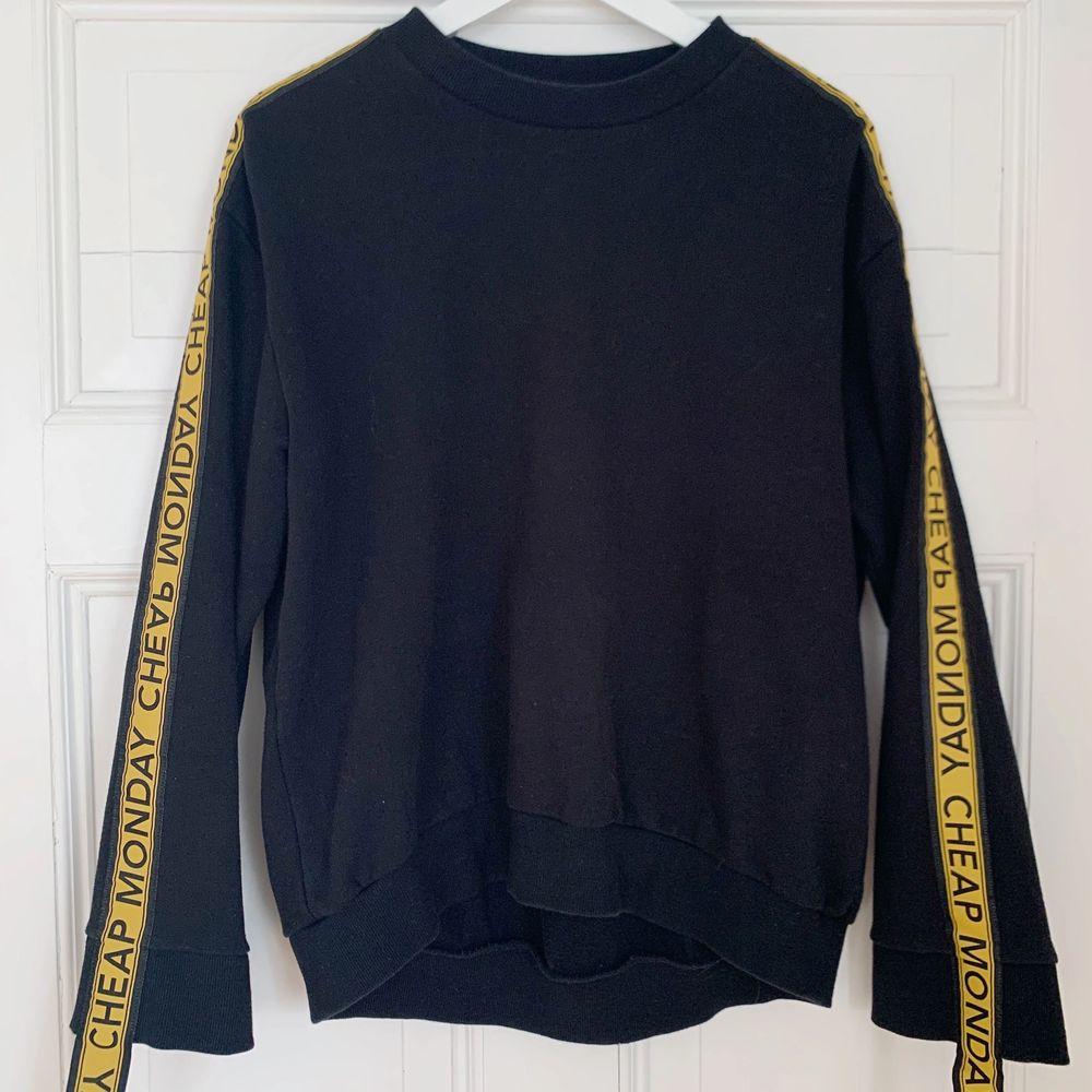 En svart sweatshirt från cheap monday med gula detaljer, köpt i London. Köparen står för eventuell frakt📦. Tröjor & Koftor.