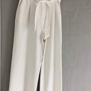 Härliga vita kostymbyxor med fin midja och knytband! De är helt raka i passformen vilket jag tycker är supersnyggt + ett fint tjockare material. Använda endast ett fåtal gånger då jag tycker de är lite små för mig. De passar 34/36 beroende på önskad passform. Köparen står för frakt💜