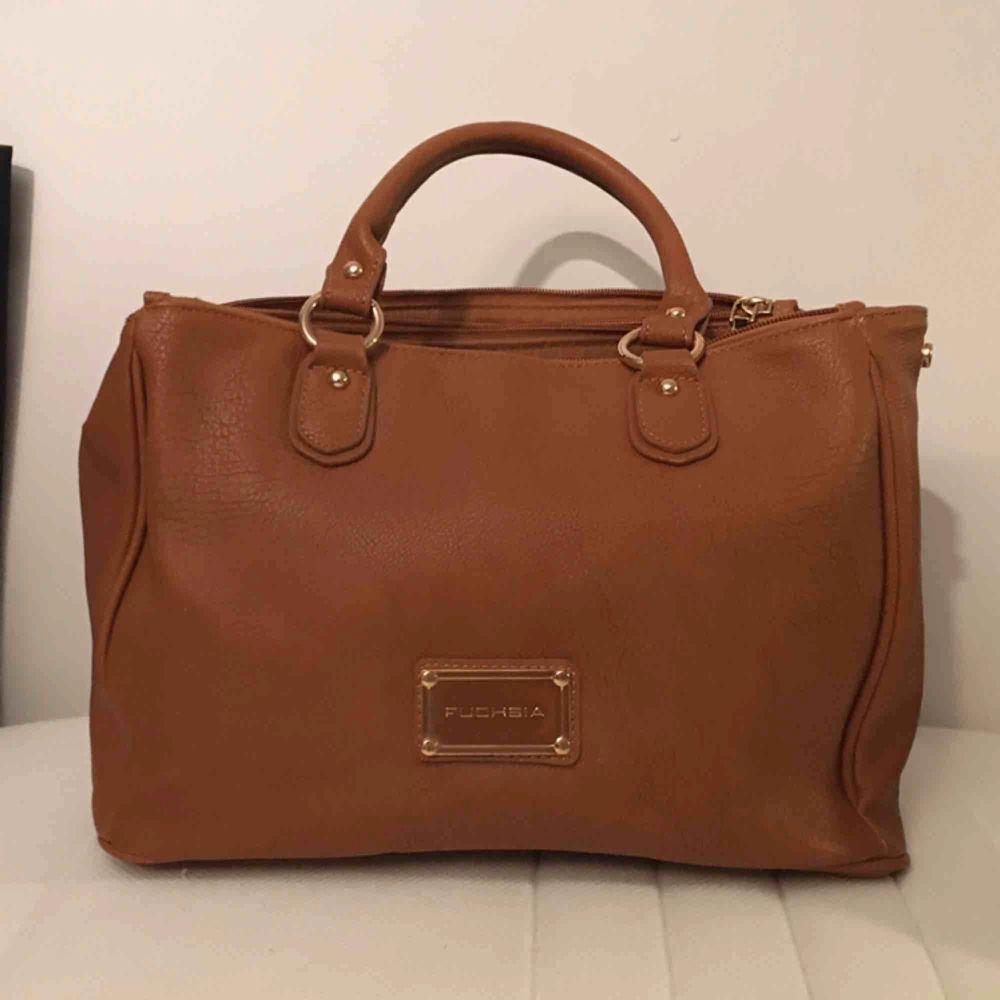 Jättefin brun läderväska (fejkläder) från Fuchsia med guldetaljer, tre rymliga fack och ett litet. Med väskan kommer också en tillhörande axelrem. Aldrig använd så i mycket fint skick😊. Väskor.