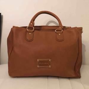 Jättefin brun läderväska (fejkläder) från Fuchsia med guldetaljer, tre rymliga fack och ett litet. Med väskan kommer också en tillhörande axelrem. Aldrig använd så i mycket fint skick😊