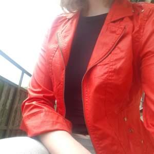 Röd statement jacka m. dekoratova nitar på fickorna och axlarna. Jackan är ifrån 2biz och är i storlek S. Priset är 150 kr exkl frakt men bjuder på frakten vid köp över 300kr.