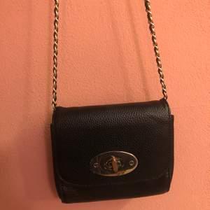 En svart liten väska med guld detaljer. Köpt på glitter och är väl använd, den har en liten fläck inuti väskan som knappt syns och märken från den som stänger på framsidan av väskan, annars bra skick!🥰📦