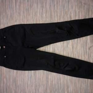 Svarta kostymbyxor. Låga i midjan. Rörliga. Fickor fram