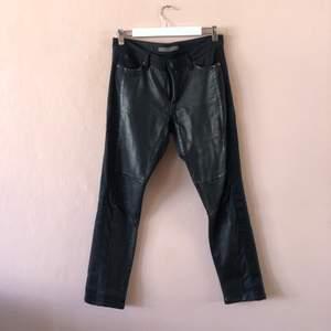 Supercoola läderbyxor med snygga detaljer. Det är läder på framsidan av byxan. Blå rivärer i stretchigt tyg och sedan svart stretchigt jeanstyg på baksidan av byxan.