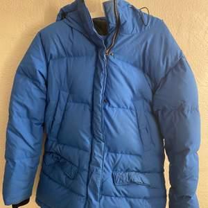 Tjock blå vinterjacka med fyra fickor framtill, två innerfickor och en ficka för hörlurar. Den har samt en elastisk mudd med tumhål i ärmsluten. Perfekt till en kall vinterdag. Storlek 38 och priset för 300kr💖