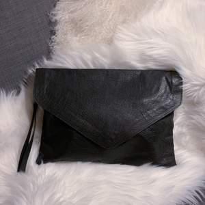 Snygg clutch / kuvertväska i aningen oversized stil. Supersnygg att bära under armen och har även ett band att ha runt handleden. Fack med dragkedja och mobilfack inuti. Sparsamt använd, nyskick. Mått: 35x25cm