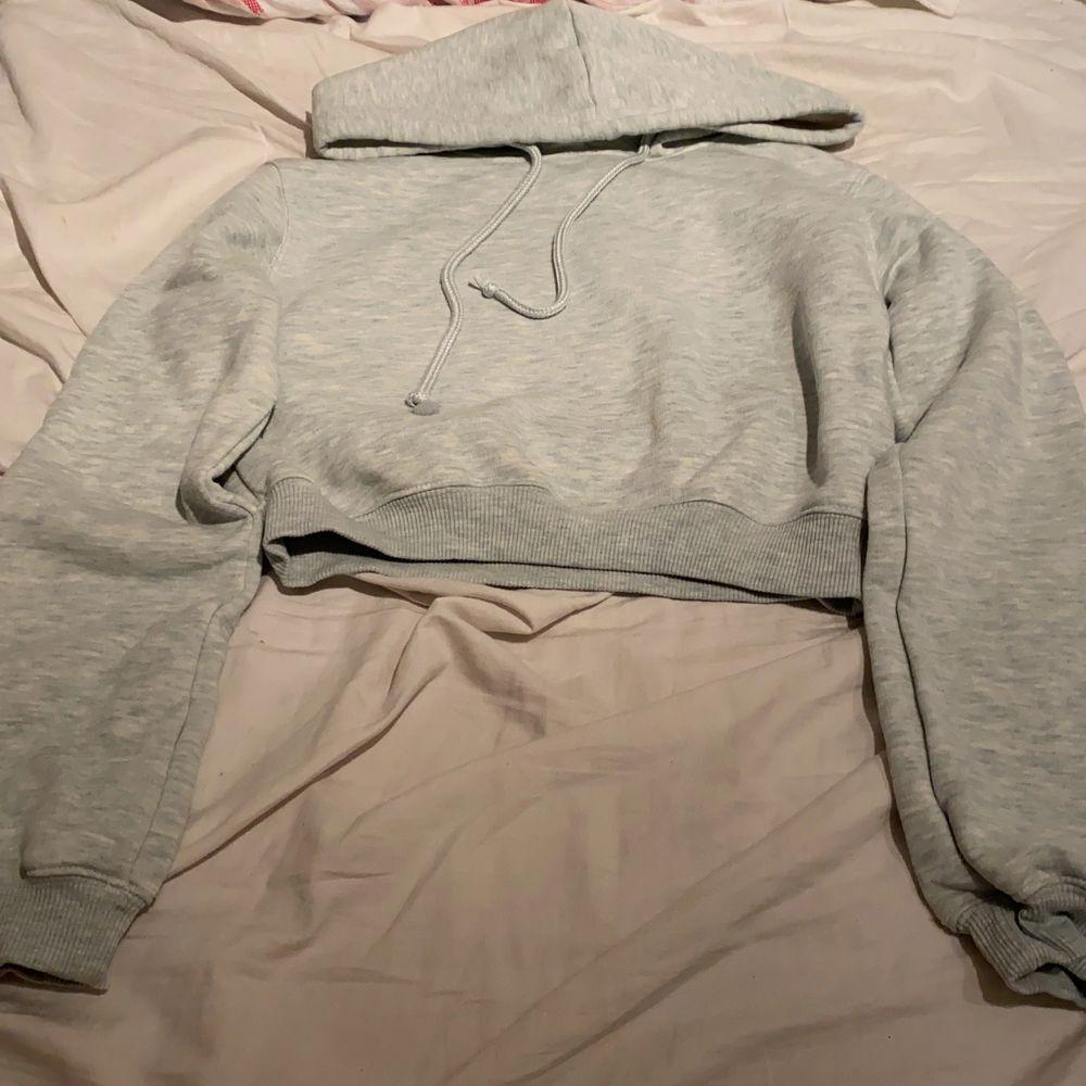 En typ blå/grå vit croppad hoodie. Tröjor & Koftor.