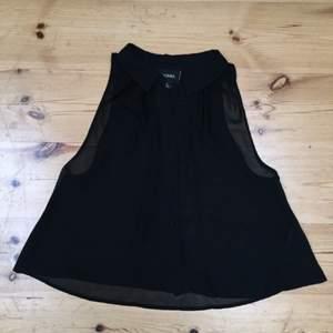 Gulligt svart linne med krage i genomskinligt tyg från monki.