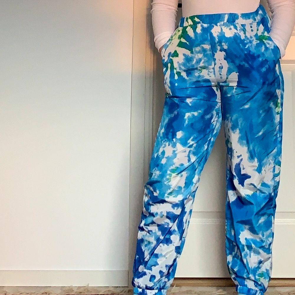 """Hej! Säljer dessa joggers i typ """"regnkläders material"""", de är  batikfärgade i blå och vit. Jag har Max andvänt de 1-2 gånger! Köpt på shein för 149kr men säljer de för endast 30kr+ frakt(45kr). De är i Storlek L men passar mig perfekt som är storlek M! Tror de även kan passa S (inte helt säker)🥰. Jeans & Byxor."""