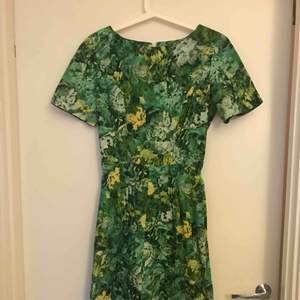 Jag är 163 och klänningen är knälång för mig. Figursydd och väldigt elegant. Den är i väldigt fint skick och näst intill orörd. Dragkedja på baksidan.