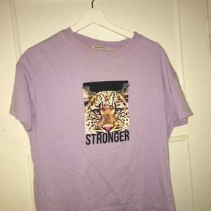 T-shirt lila med tryck.