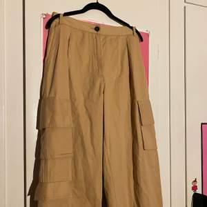 Beigea cargo pants från monki. Köpta second hand men har bara använt de en gång då de är för stora för mig:( Väldigt vida och har totalt tre fickor på benen. Kan skicka fler bilder.