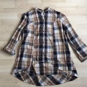 rutig oversize skjorta i bruna nyanser. rundad krage. längre baktill i rundad form🐒