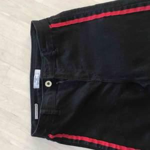 Svarta jeans med röda sträck på sidorna. Jag är storlek 25 så dom är stretchiga och passar fler storlekar. Inte mycket använda. Bara att skriva för fler frågor men frakt tillkommer