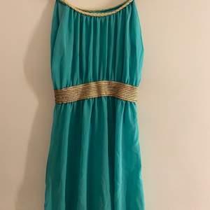 Turkosblå klänning med guld detaljer som är längre i bak, köparen står för ev frakt