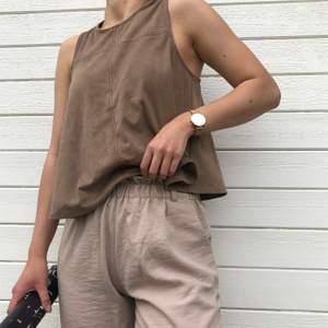 tank top/linne i brun mockaimitation (materialet syns tydligare på andra bilden). svänger utåt och fladdrig så inte alls för varm till sommaren! guldfärgad knapp bak. använd sparsamt!! modellen är 163 cm lång.