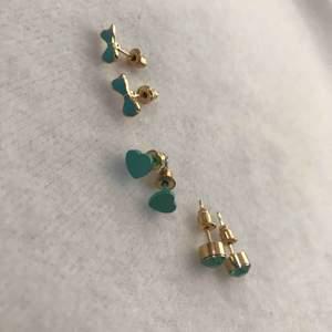 Tre blåa örhängen, hjärt formad, en med fake blå kristall och en rosset formad. Har bara testat på den hjärt formade, annars aldrig använt. De två andra är helt oanvända.