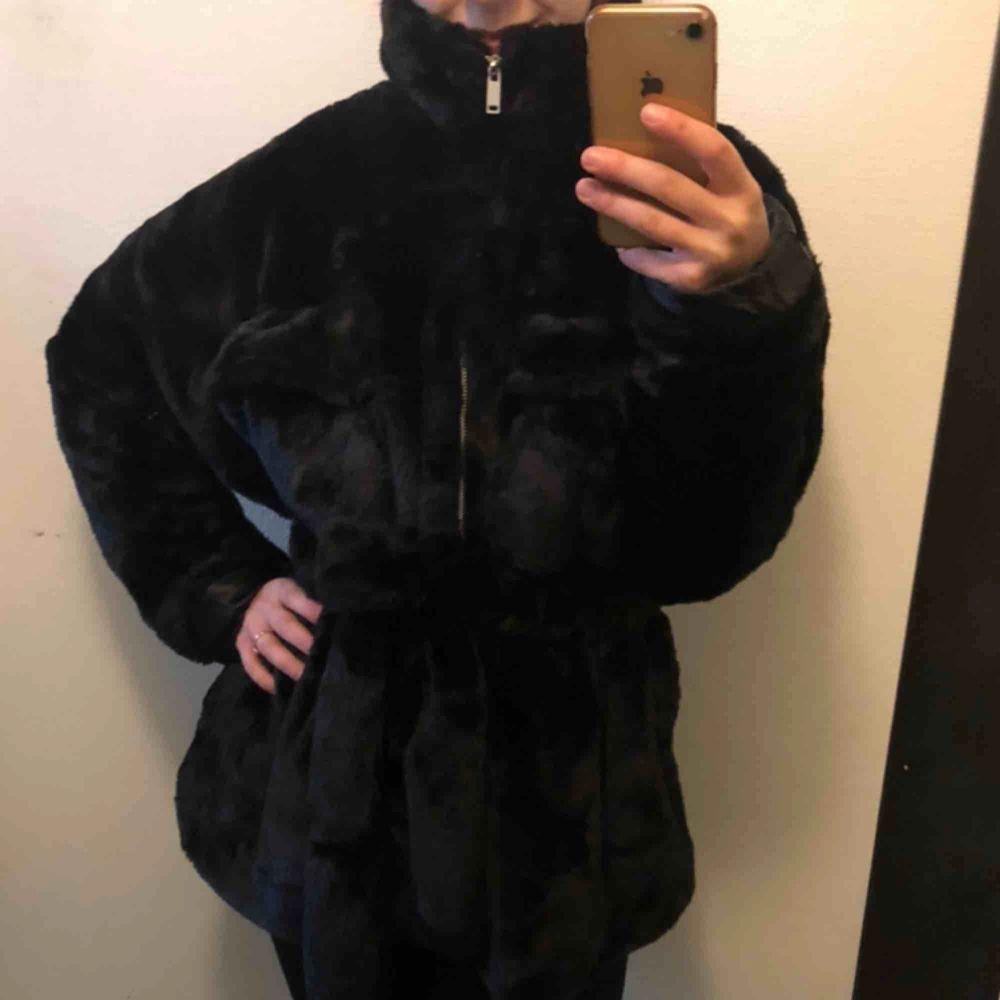 Svart jättefin faux fur kappa med knytning som markerar midjan samt dragkedja hela vägen upp i kragen. Så mjuk, mysig och varm! Helt oanvänd, prislapp kvar. Säljer pga har för många jackor.  Kan mötas upp i Sthlm, annars tillkommer frakt . Jackor.
