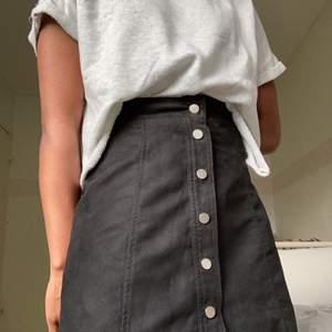 Svart kjol i mockaimitation med silvriga tryckknappar. Är ganska liten så den var en aning stor i midjan men annars fin passform. Fint skick