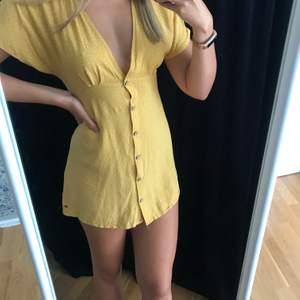 Gul prickig klänning från Pull & Bear i storlek Medium.