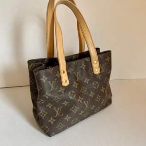 LV (fake) väska, second hand. Mått: H 18 cm x B 23 cm x D 11cm. Handtag ca 35 cm. Så bra skick! Finns dock en liten fläck på insidan/ fodret. Frakt ingår på denna annons.