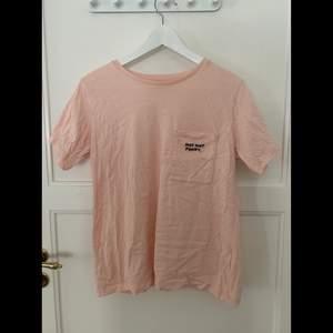 T-shirt med brodyr på bröstficka, mer som en M