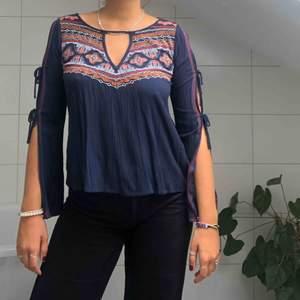 Sjukt fin långärmad blus som passar perfekt till sommar festivaler! Den är mörkblå med olik mönstrade broderingar.