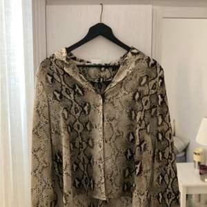 En skjort blus med orm mönster, från vila clothes, storlek 36, knappt använd. Kunden står för frakten