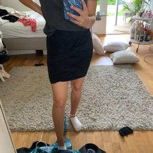 Svart kort kjol med knutar som detaljer. Använd en gång