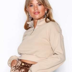 En beige croppad tröja med dragkedja från Nelly. Ordinarie pris är 299kr. Knappt använd fint sick